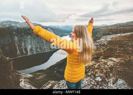 Young woman happy raised hands on mountain top travel adventure lifestyle journey vacations aerial lake landscape success wellness emotions - Stock Photo