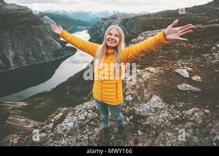 Happy girl success raised hands standing on mountain summit hiking travel adventure lifestyle vacations weekend getaway aerial  lake landscape in Norw - Stock Photo