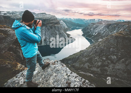 Man travel photographer taking photo landscape in Norway mountains standing on cliff hobby lifestyle adventure vacations lake aerial view - Stock Photo