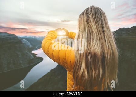 Woman traveling in sunset mountains hands heart symbol shaped Lifestyle emotional concept vacations weekend getaway aerial Norway landscape - Stock Photo