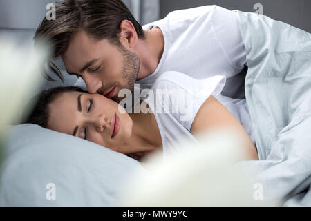 Husband tenderly kissing sleeping wife in bed - Stock Photo