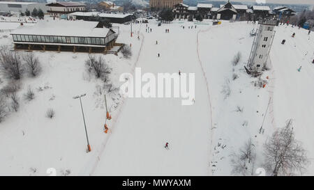 Aerial view: Skiers and snowboarders going down the slope in winter day. Skiers and snowboarders enjoying on slopes of ski resort in winter season. - Stock Photo