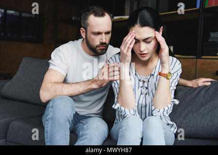 husband asking forgiveness from wife after quarrel at home - Stock Photo