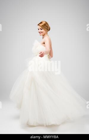 beautiful bride in white wedding dress, isolated on grey - Stock Photo