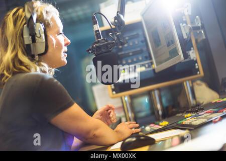 White British female radio DJ inside recording studio at work - Stock Photo