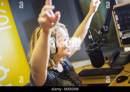 White British female DJ working inside recording studio with headphones - Stock Photo