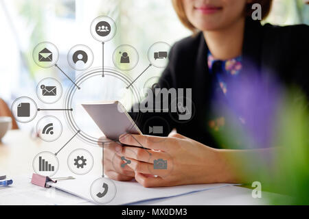 Woman using smartphone in office with visual icon technology concept. - Stock Photo
