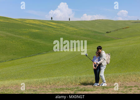 San Quirico, Italy; 10th May 2018; A young Adult tourist Couple Taking a Selfie in Front of a Typical Tuscany Countryside Scene - Stock Photo