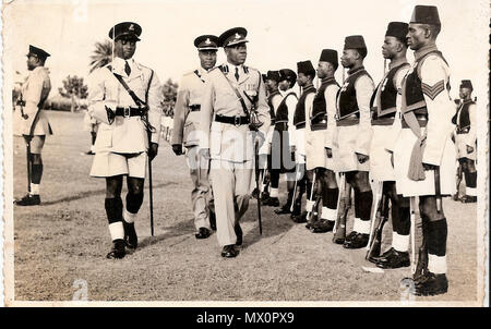 . English: He rapidly rose through the ranks and was promoted to an Assistant Superintendent of Police in 1949, one of the only four Africans to attain that rank at a period when nationalistic fervour was at its peak and the Colonial Government viewed each Nigerian with suspicion. He attended several courses in the United Kingdom including Police College Ryton –on-Dunsome in 1956, and proceeded to Police College Kincardine Scotland in 1960. 21 September 2014, 07:22:23. Wole Soyinka 456 Olufunwa Inspecting A Parade - Stock Photo