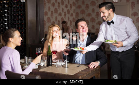 Polite smiling waiter bringing ordered dishes to guests at restaurant - Stock Photo