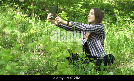 Teenage girl using tablet and taking selfie photo in green park. Cute young girl with digital tablet in a summer forest. - Stock Photo