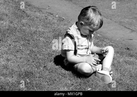 young boy in deep thought sitting on grass black and white photograph - Stock Photo