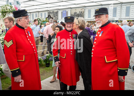 A visitor to the RHS Chelsea Flower Show in London , UK gives a Chelsea Pensioner a kiss on the cheek. - Stock Photo