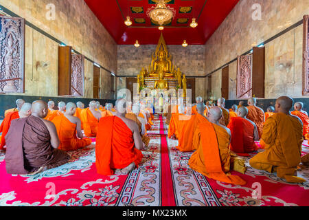 Kanchanaburi, Thailand - September 16, 2016: Buddhist monks celebrate the month of merit festival by chanting in front of golden Buddha image in beaut - Stock Photo