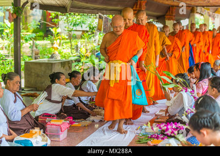 Kanchanaburi, Thailand - September 16, 2016: Buddhist Mon people celebrate the month of merit festival by offering flowers to monks in Sangkhlabri, Ka - Stock Photo