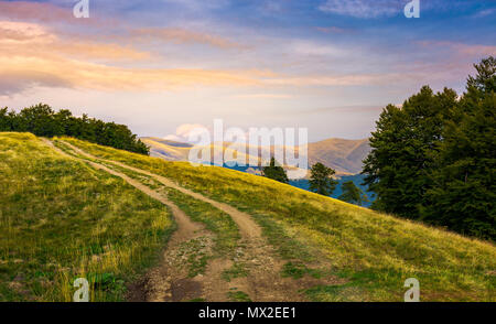 mountain road uphill in to the beech forest. Svydovets mountain ridge in the distance. beautiful clouds in reddish light on a blue evening sky. stunni - Stock Photo
