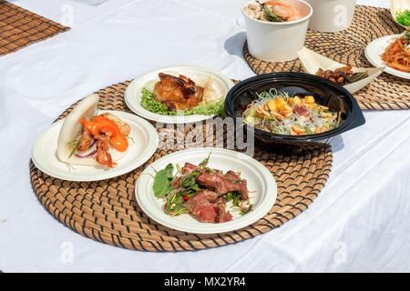 food samples, variations of diverse Asian dishes served on trays during the Asian street farmers market. Soft shell Crab Bao, roasted silkworm, Tom Yu - Stock Photo