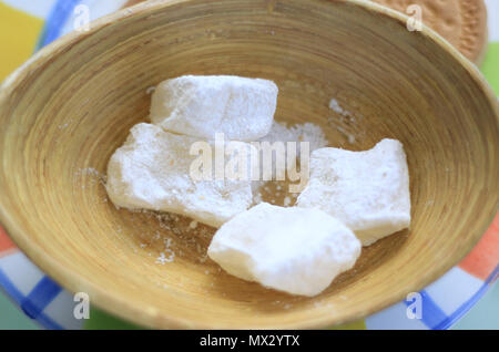 Loukoum cubes covered in white powedered sugar in a wooden plate. - Stock Photo