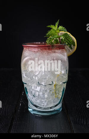 Variation of gin and tonic cocktail with cherry syrup in skull cup - Stock Photo