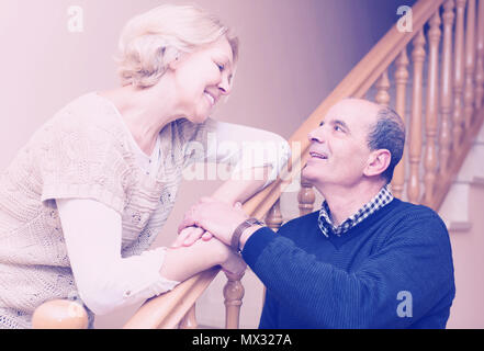 Happy loving senior family couple posing near staircase at home - Stock Photo