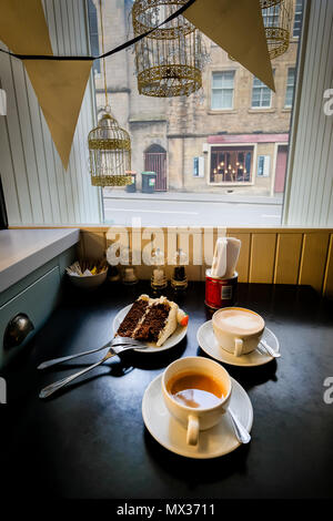 cup of tea, cappuccino and a red velvet cake on a plate on the window sill of a small cafe. - Stock Photo