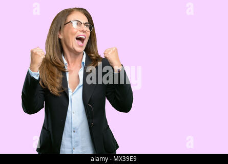 Middle age business woman happy and excited expressing winning gesture. Successful and celebrating victory, triumphant - Stock Photo
