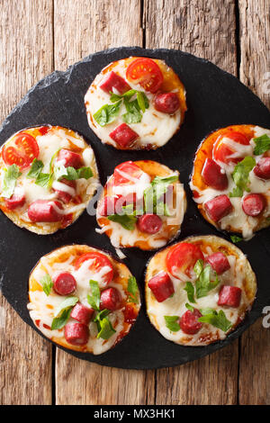 Appetizing of baked eggplant with cheese, tomatoes, sausages and herb close-up on the table. Vertical top view from above - Stock Photo