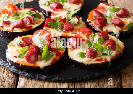 Mini pizza from eggplants with mozzarella, tomatoes, sausages and greens close-up on the table. horizontal - Stock Photo