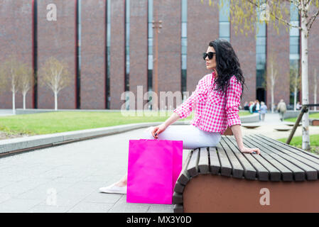 A young and beautiful girl resting on a bench after shopping. A woman in sunglasses relaxes outdoors. - Stock Photo
