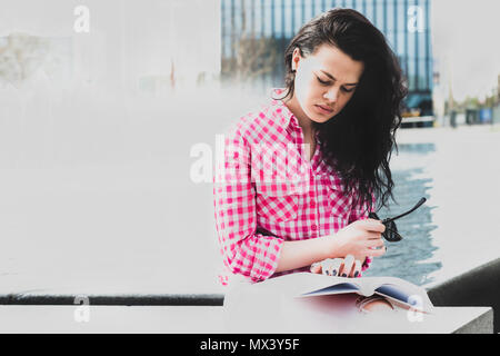Focused woman reading a book by the fountain. A pretty girl is studying for the exam. Cute female reading a book resting after a hard day. Lifestyle c - Stock Photo
