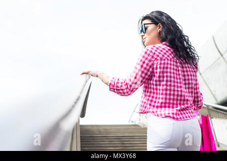 A young and beautiful girl goes up the stairs after shopping. Silhouette of a woman satisfied with shopping. Concept lifestyle. - Stock Photo