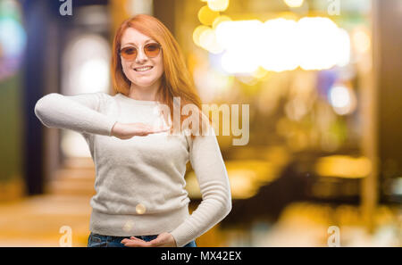 Beautiful young redhead woman holding something, size concept at night - Stock Photo