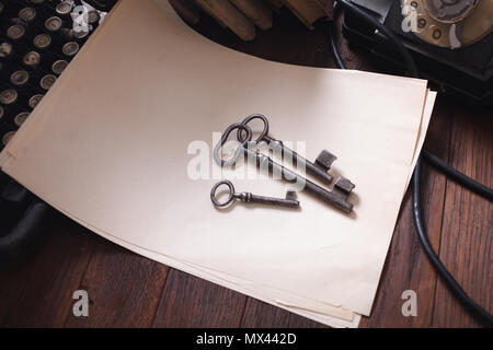 Old retro phone with vintage typewriter and a blank sheet of paper on wooden table - Stock Photo