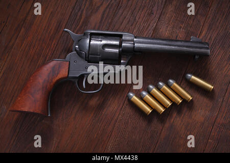 Old western revolver with cartridges on wooden table - Stock Photo