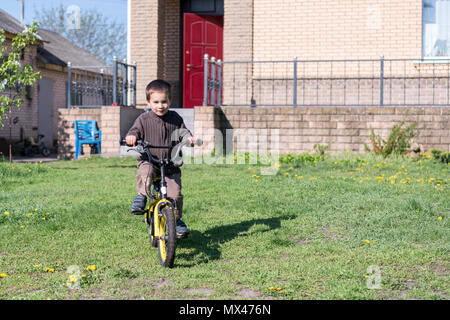 a boy rides his bike on a hot summer day. Boy riding a bicycle in the yard on a background of a brick house. - Stock Photo