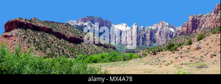 Panoramic view of sandy valley and green trees backed by steep colorful mountain walls under a bright clear blue sky. - Stock Photo