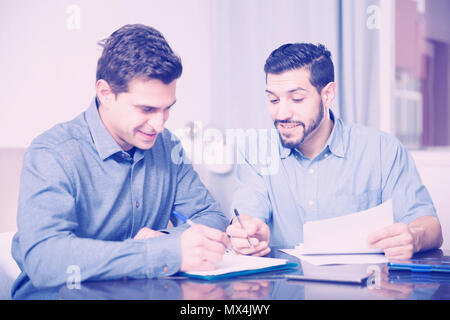 Portrait of two cheerful young men reading documents together at home table - Stock Photo