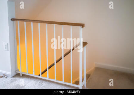 Interior inside house home, townhouse with stairs, steps or staircase leading down to basement level with yellow light lamp glowing, railing - Stock Photo