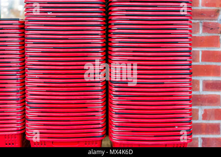 Closeup of generic red shopping baskets stack stacked in front of store outside exterior by brick wall many pattern - Stock Photo
