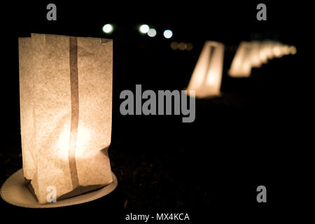 Christmas Eve candle lights flame closeup illuminated in paper bags on plates at night in row lining street road by residential neighborhood house dec - Stock Photo