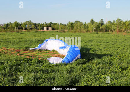 pilot newcomer paraglider is trained on the ground to lift up and hold the blue-white paraplane. - Stock Photo