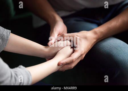 Close up of couple holding hands, giving psychological support c - Stock Photo