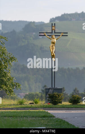 Jesus Christ on cross, golden statue against green natural background - Stock Photo