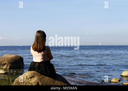 Girl sitting on a stone, looking at the blue sea. Summer, sun, s - Stock Photo