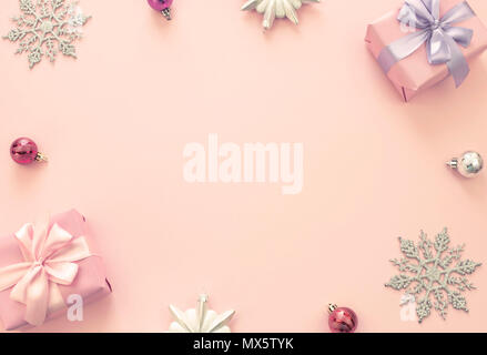 Christmas composition Flat lay boxes with gifts satin ribbon bow Christmas toys snowflakes. Decorative frame top view pink background - Stock Photo