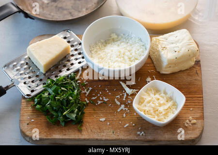 Frittata ingredients: Whisked eggs & milk, halloumi and parmesan cheese, cut basil - Stock Photo