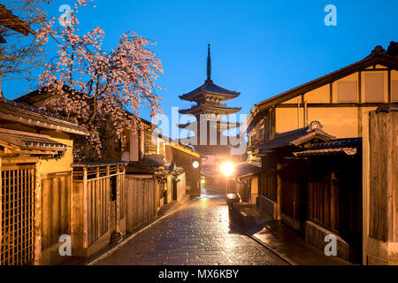 Japanese pagoda and old house with cherry blossom in Kyoto at twilight. - Stock Photo