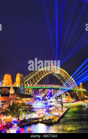 The Sydney Harbour bridge arch during Vivid Sydney light show and festival illuminated with bright blue laser beams in dark night sky. - Stock Photo