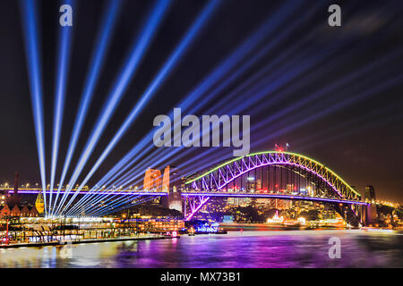 Vivid sydney festival of light and ideas in Sydney city CBD around Harbour with light beams off the Harbour bridge from circular Quay. - Stock Photo