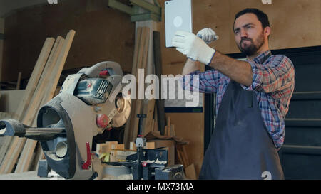 The carpenter makes selfie on tablet in the workshop near electric saw. Professional shot on Lumix GH4 in with high 4K resolution. You can use it e.g  - Stock Photo